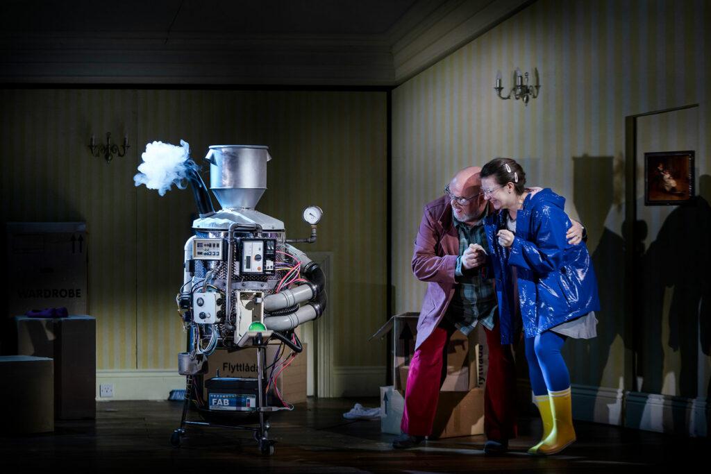 Coraline och hennes pappa står nerhukade tillsammans och tittar på något som ser ut som en robot.
