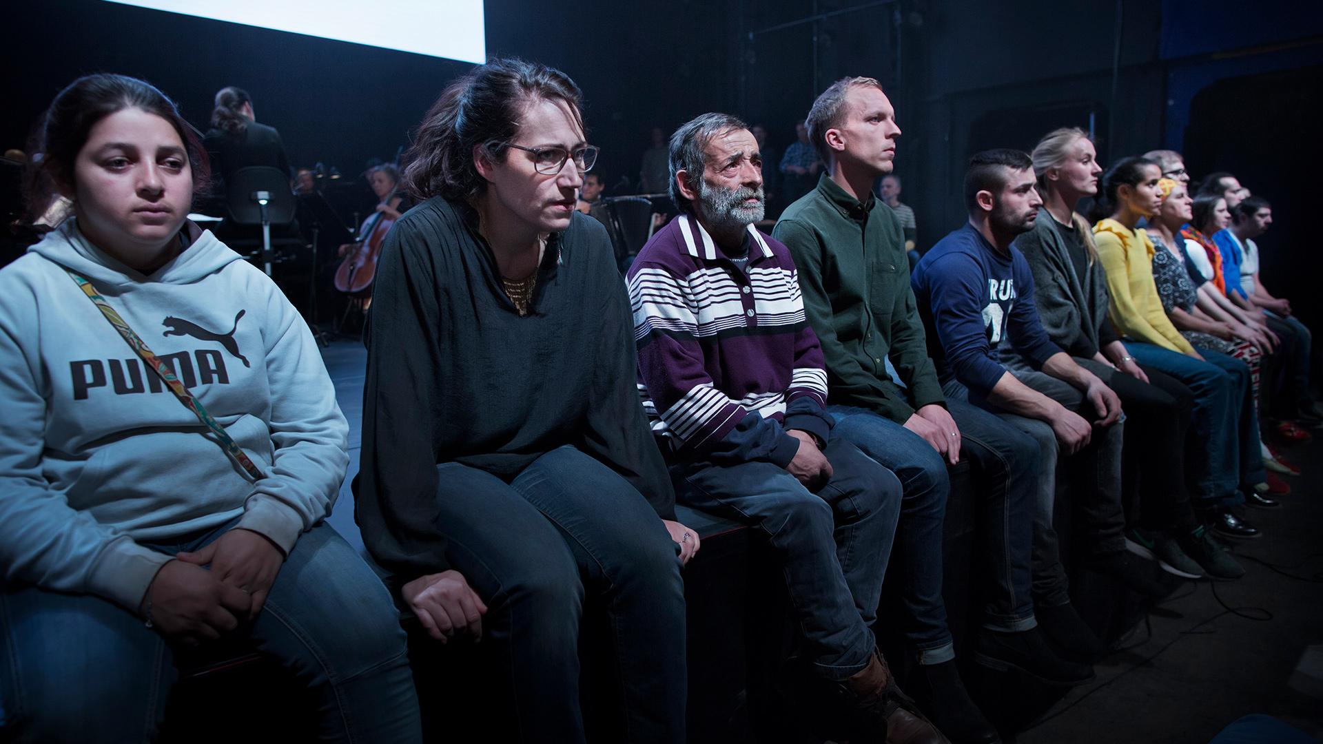 Ensemblen i Förklädd gud sittandes på rad.