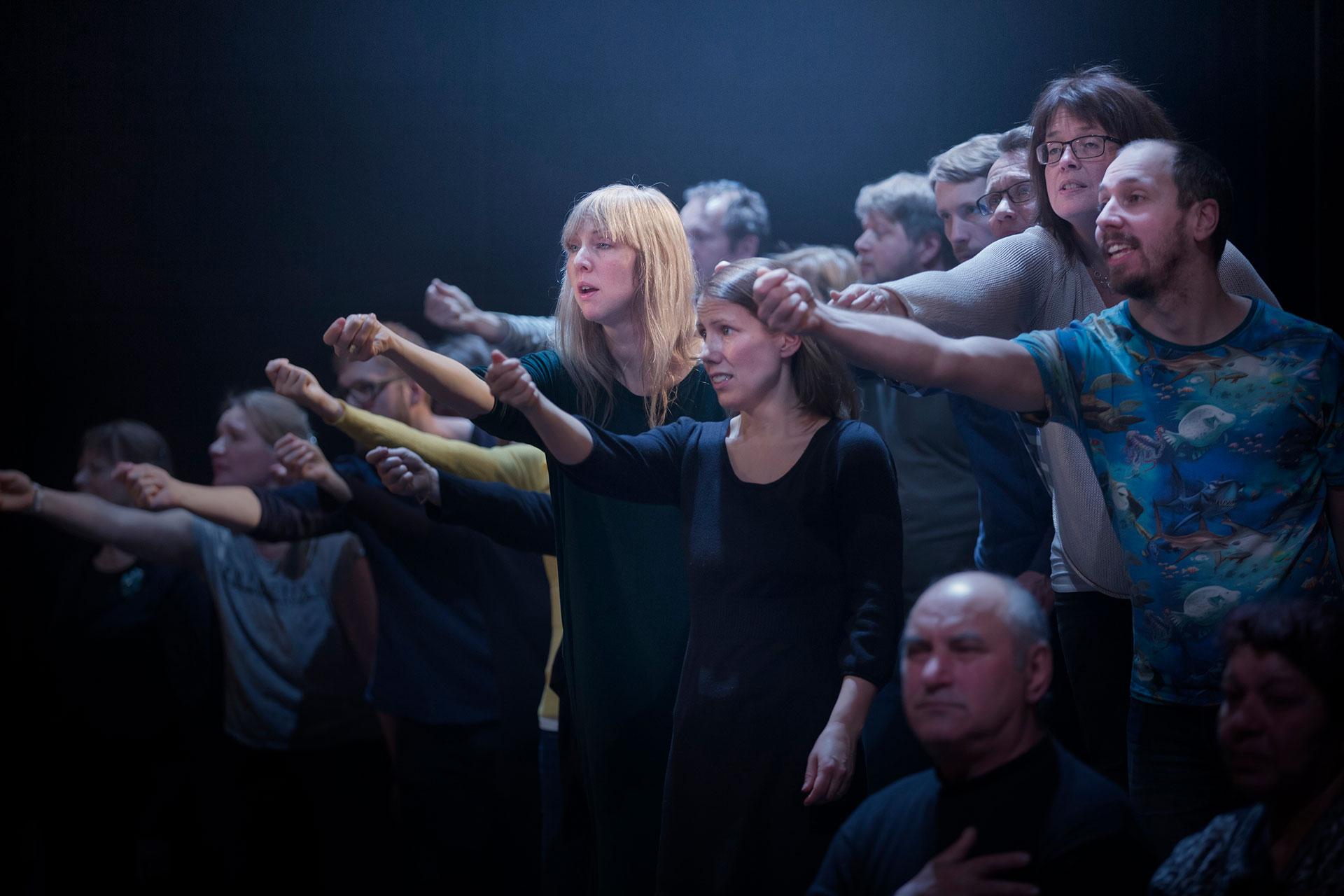 Ensemblen i Förklädd gud sträcker ut sina händer.