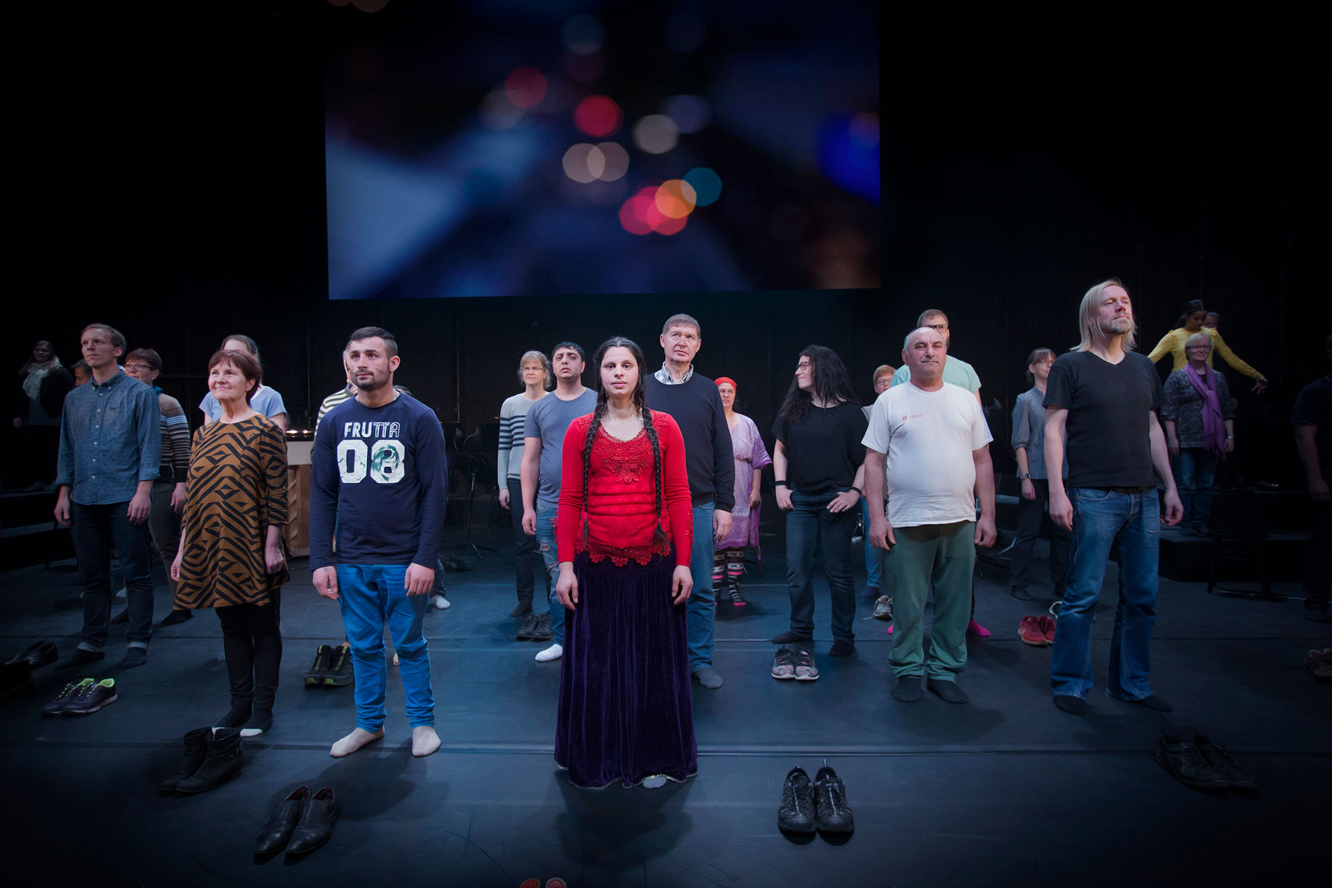 Ensemblen i Förklädd gud står samlade på scenen, alla har tagit av sig sina skor.