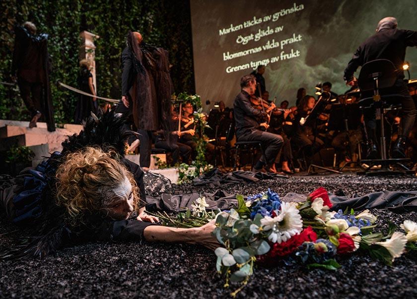 En ung kvinna i svart klänning ligger på vad som ser ut som aska. Hon sträcker sig efter en färgstark blombukett. Orkester syns i bakgrunden.