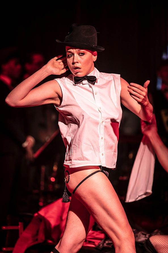 Tuff ung kvinna i svart hatt, vit skjorta, fluga och bara ben lyssnar in med handen bakom örat.
