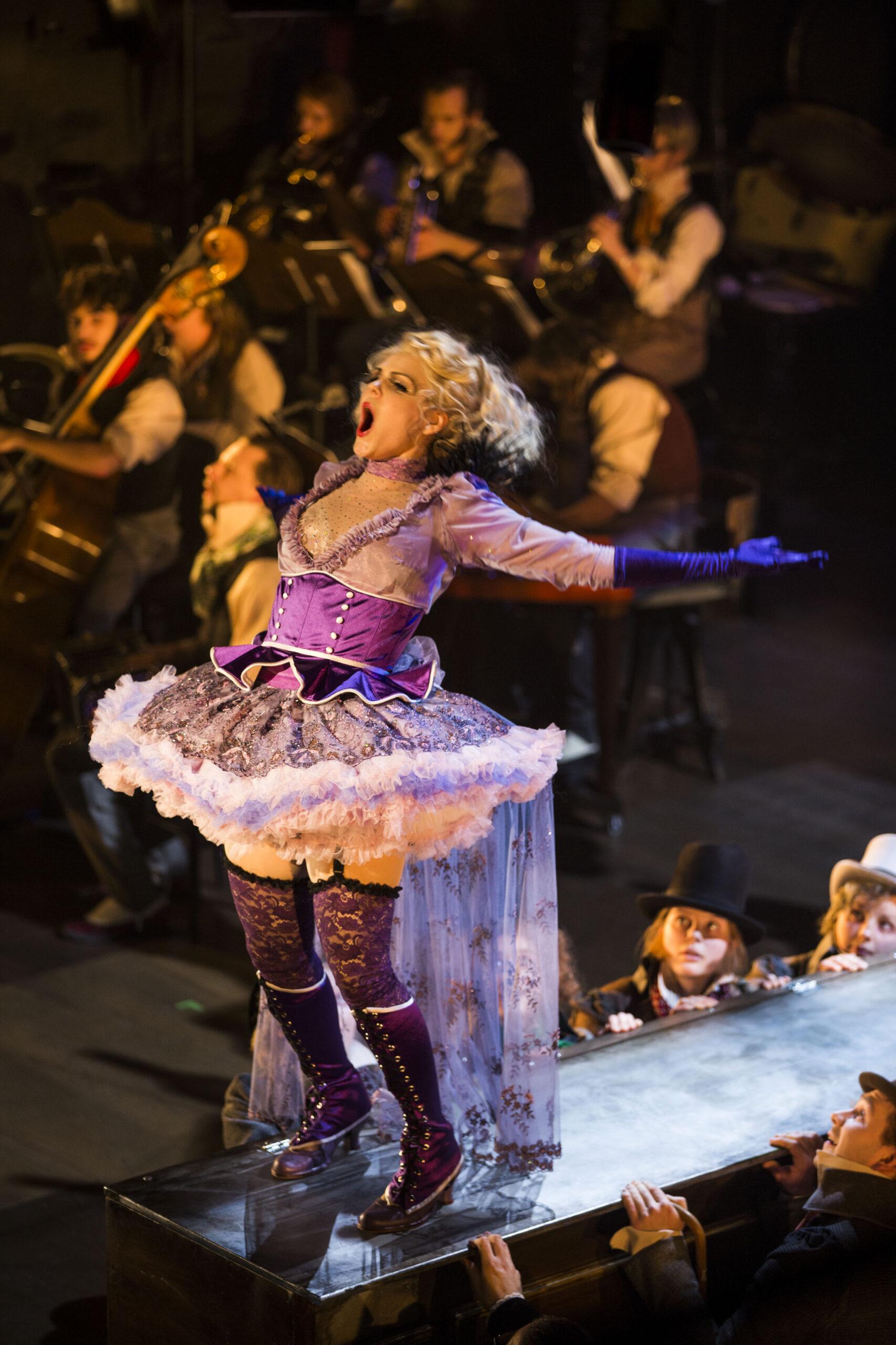 En ung kvinna i excentriska kläder sjunger för livet.