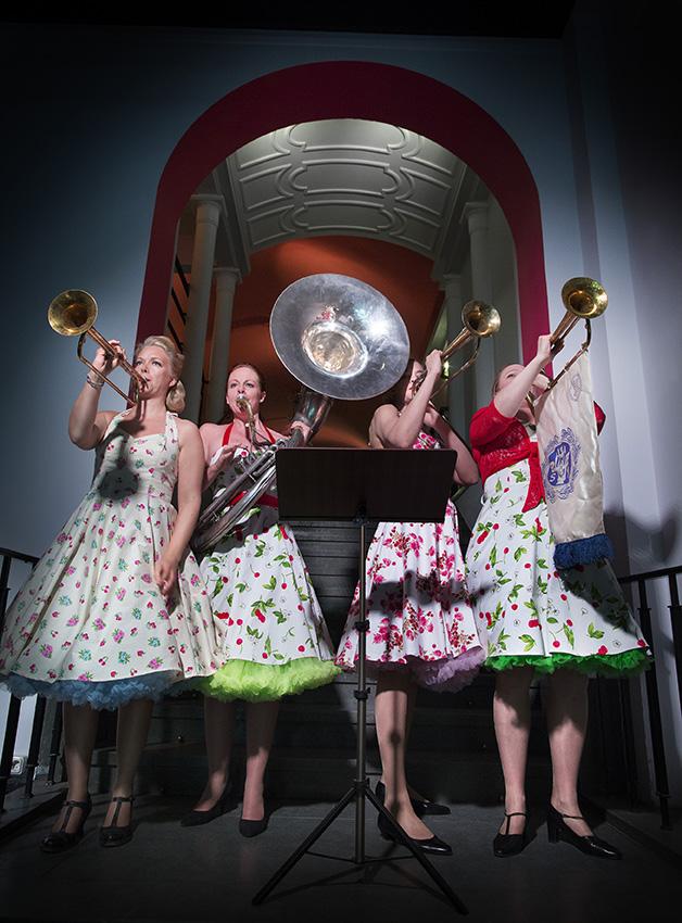 Fyra kvinnor i blommiga 50-talsklänningar trumpetar i foajén.
