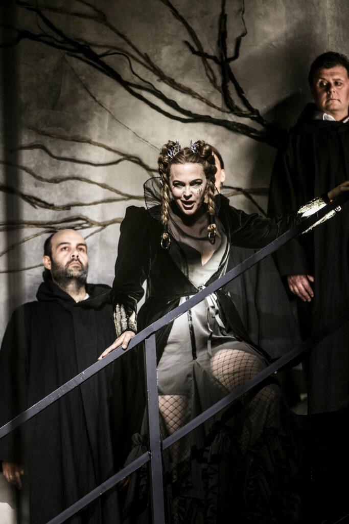 Turandot står i en trappa med två män bakom sig. Ser rakt in i kameran och ler.