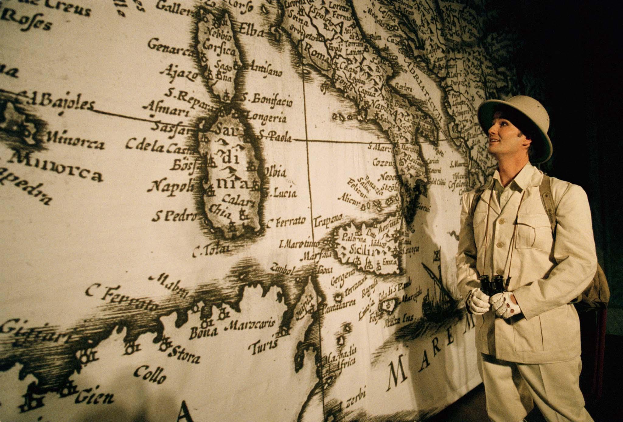 En safariklädd ung man med kikare i handen tittar förväntansfullt ut över en stor karta.
