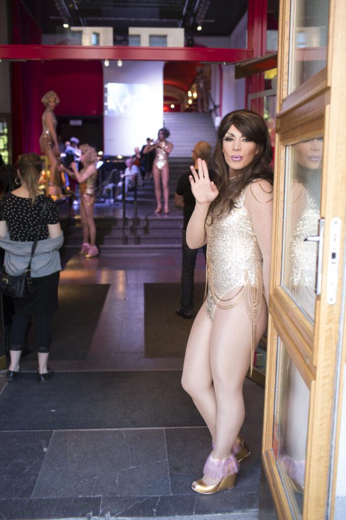 En snygg transperson i höga klackar och guldbody hälsar välkommen till Folkoperan.