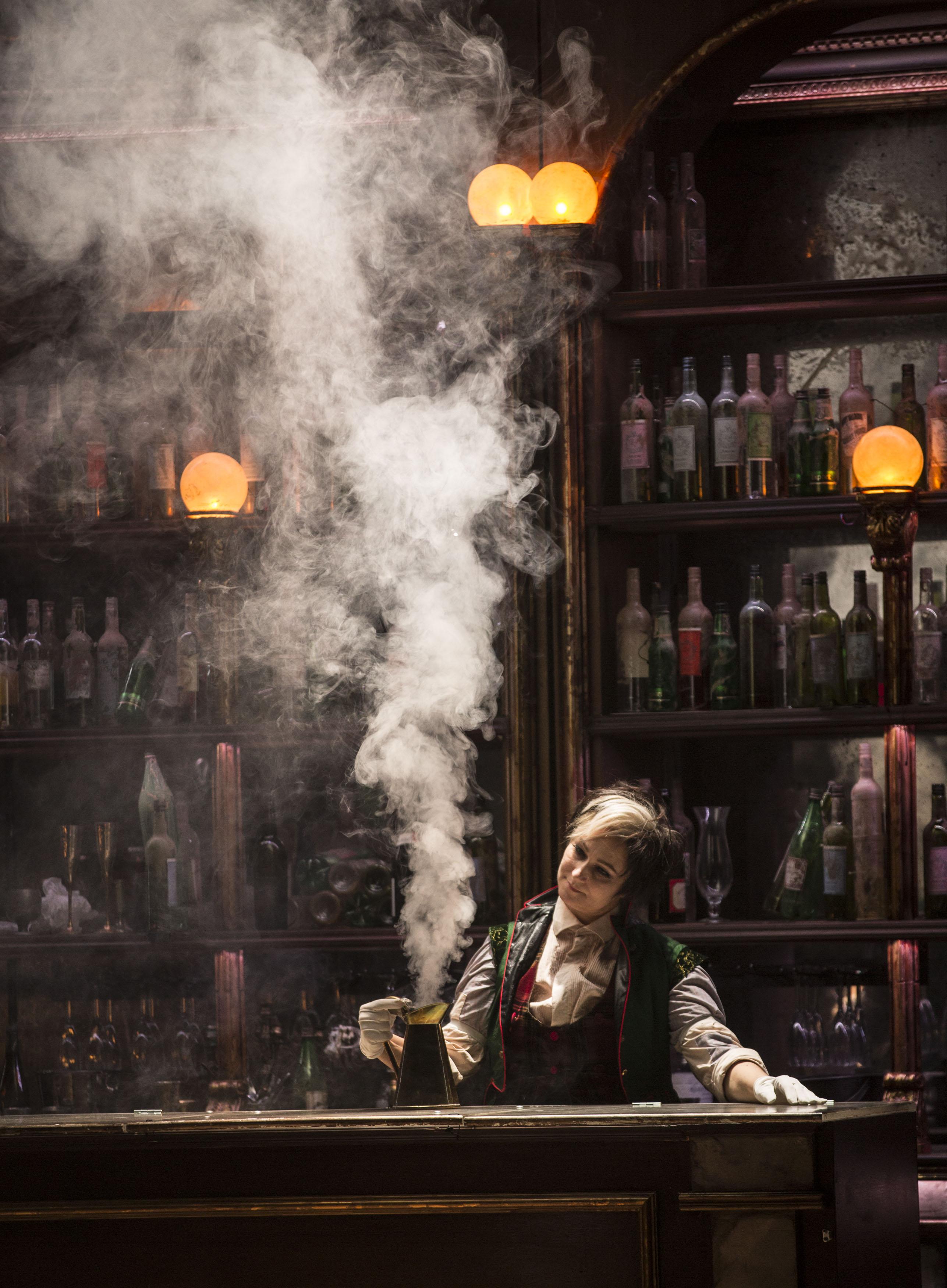 En kvinna i en bar med en ångande kanna kaffe på bardisken.