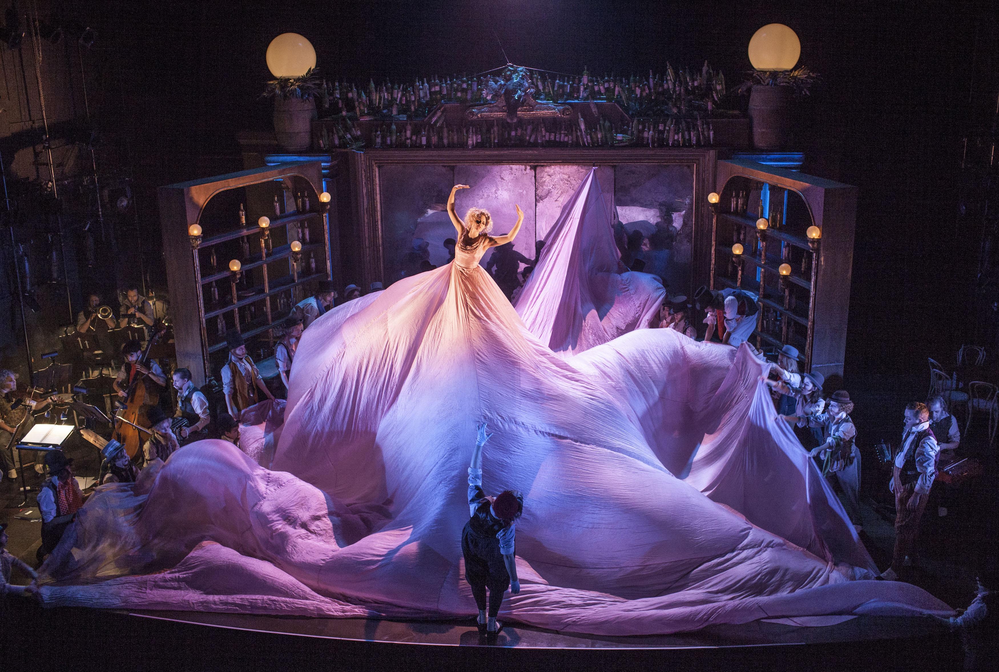 Elisabeth Meyer i en enorm rosa klänning som fyller hela scenen i Folkoperans uppsättning av Hoffmans äventyr från 2015.