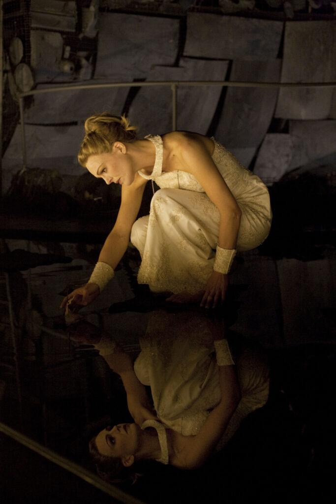 En ung kvinna iförd en vit klänning sitter på huk och speglar sig i vattnet.