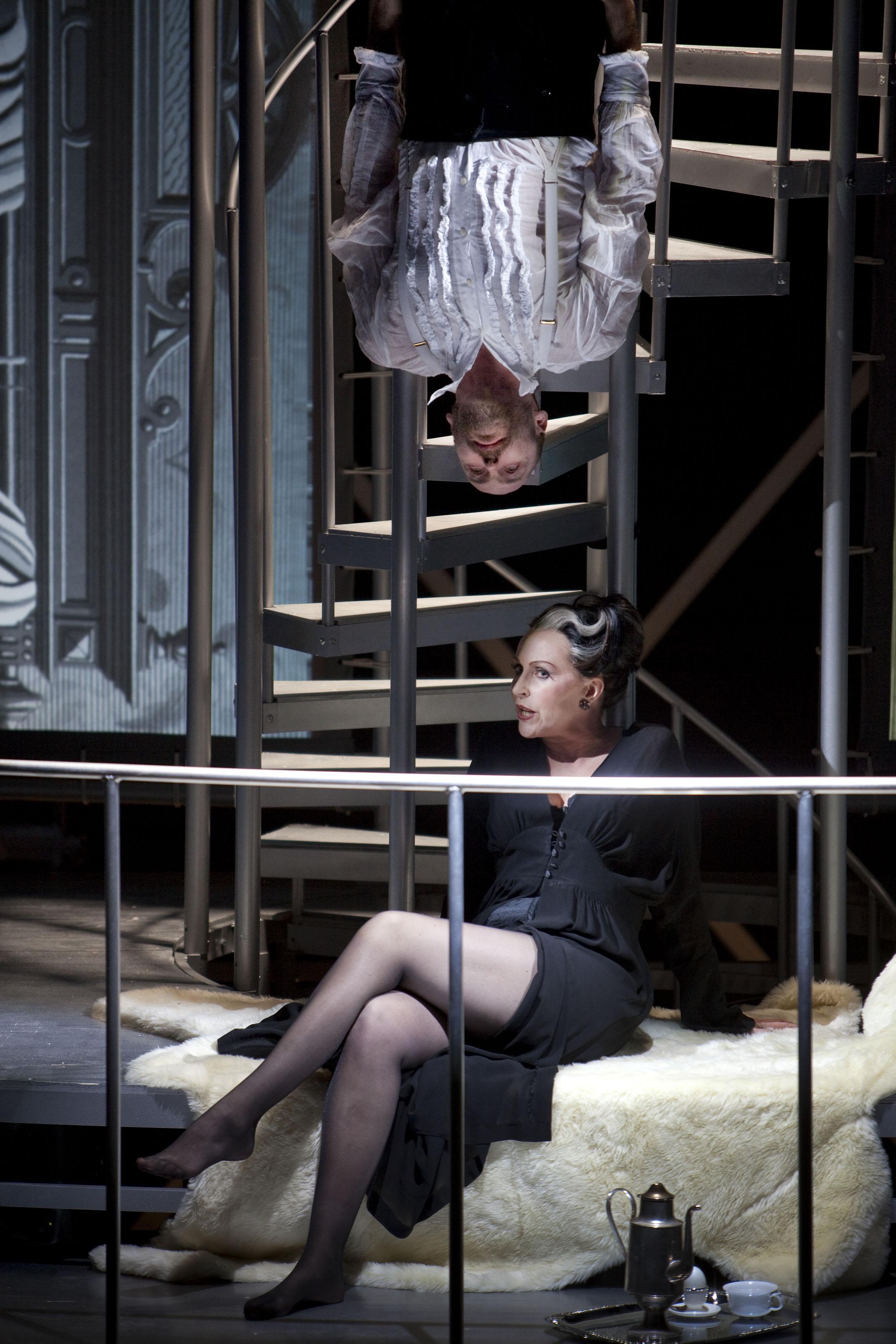 En man i vit skjorta hänger upp och ner. Nedanför sitter en Cruella-lik kvinna i svarta kläder och verkar smida onda planer.