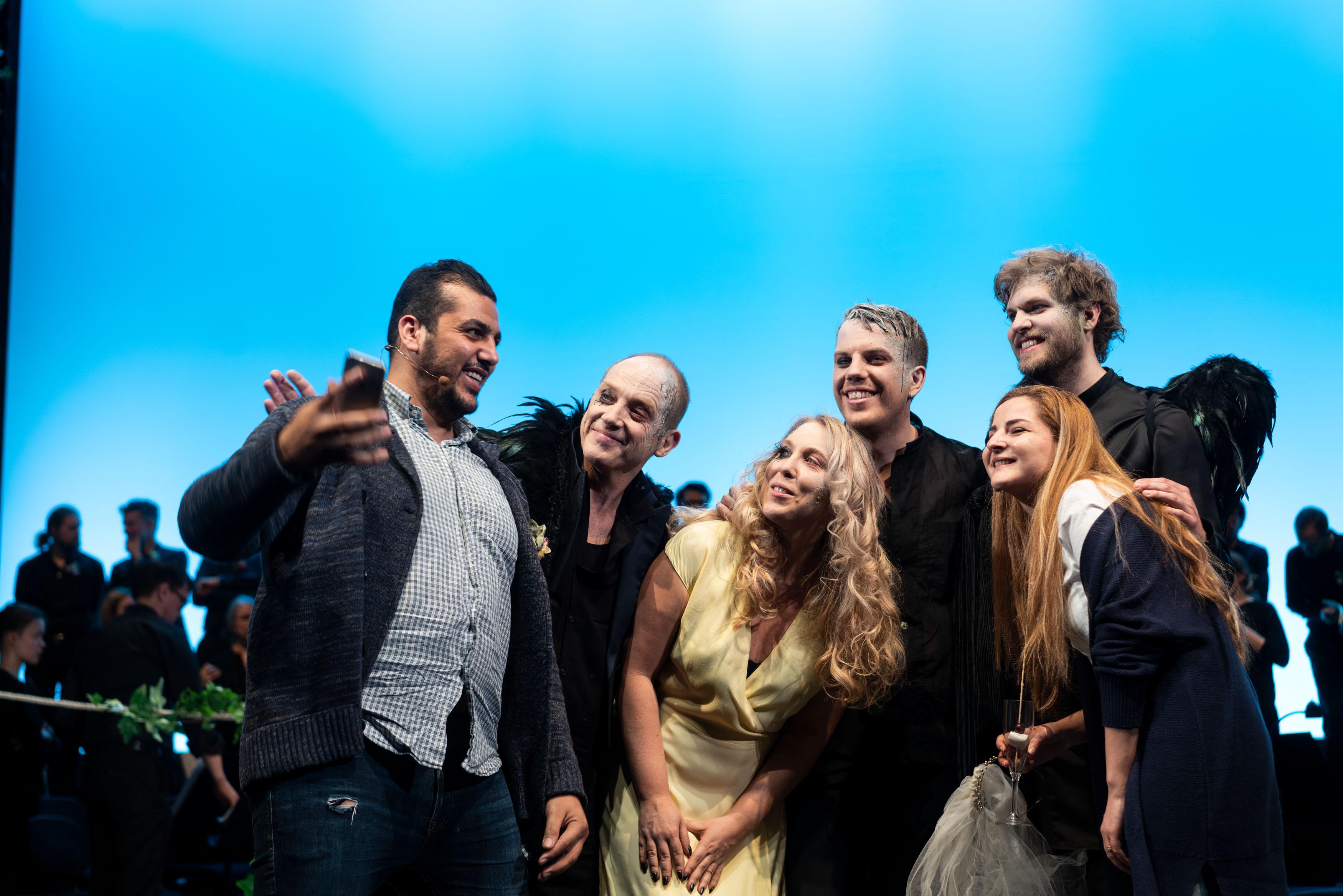 En man håller upp sin mobil för att ta en selfie tillsammans med några kostymklädda skådespelare.