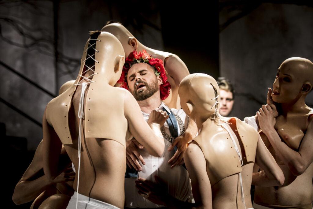 Maskklädda figurer står samlade kring en ung trånande man med röd blomkrans i håret.