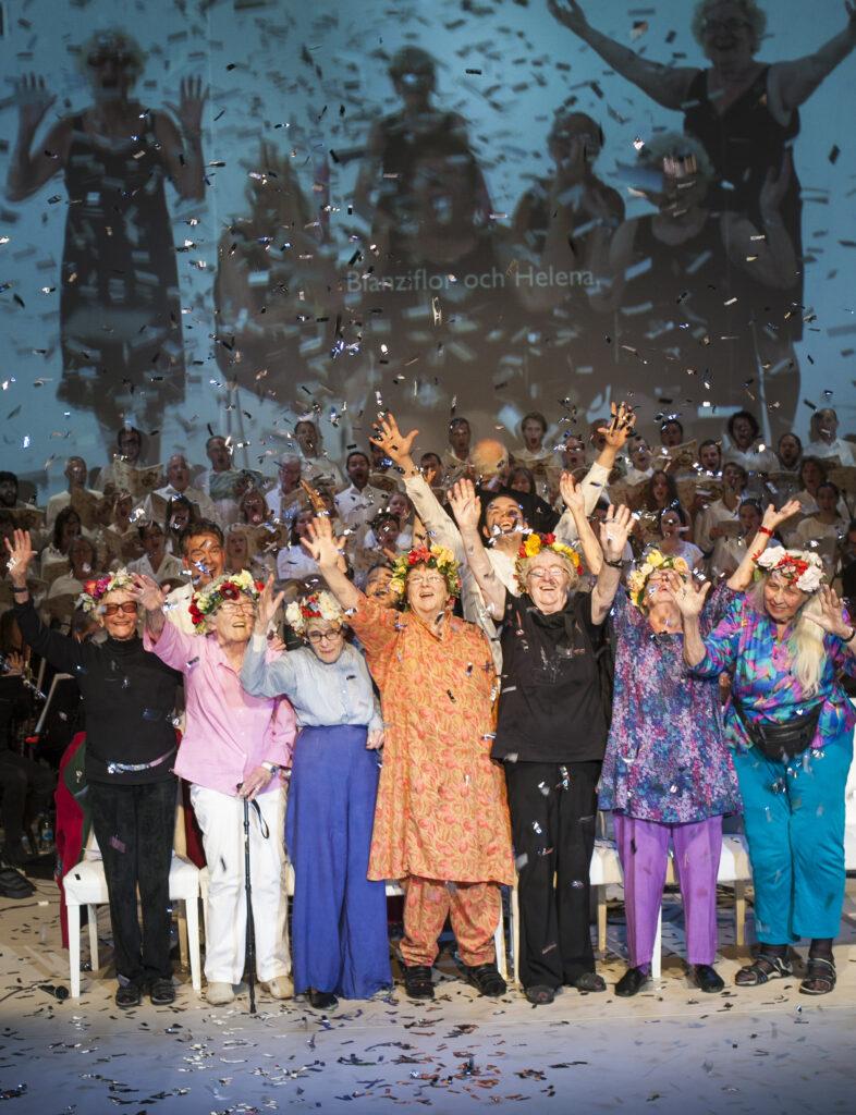 Ett gäng äldre kvinnor sträcker händerna i luften. Det regnar konfetti.