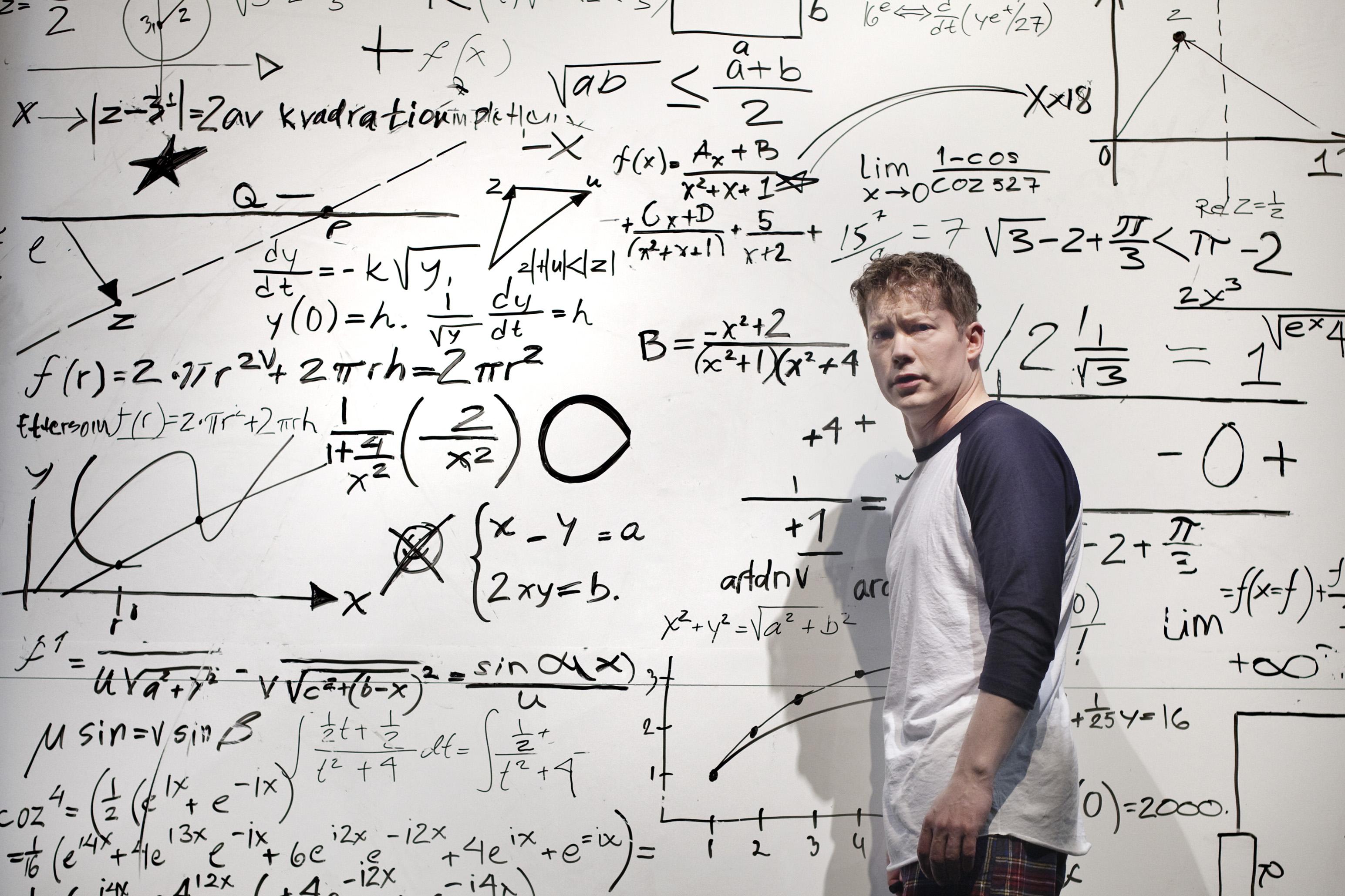 En ung man ser förbryllat in i kameran. Bakom en withe board full med komplicerade ekvationer och tal.