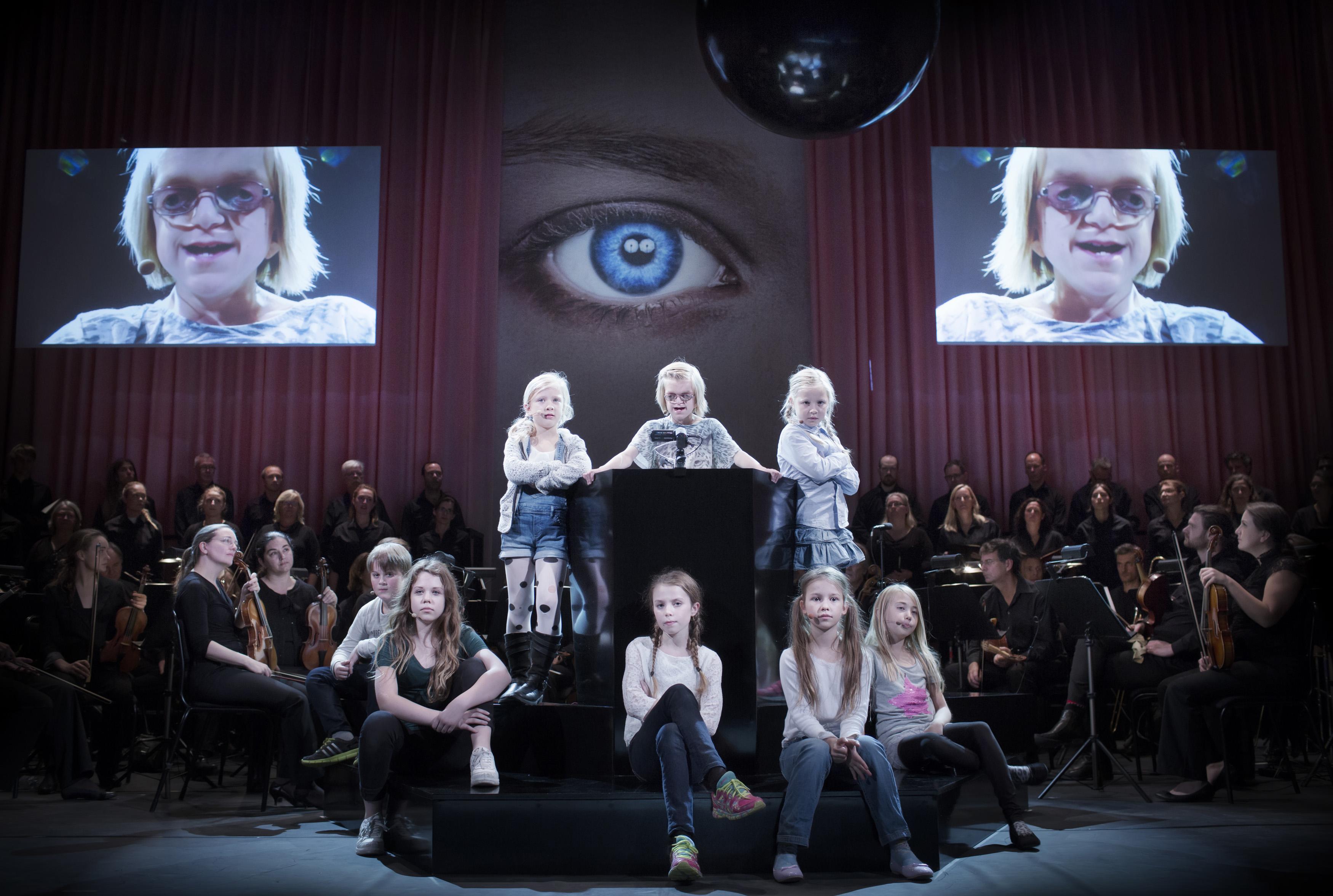 Sju barn tittar allvarligt på oss från ett podium. I bakgrunden svartklädda korister i det rosa rummet.