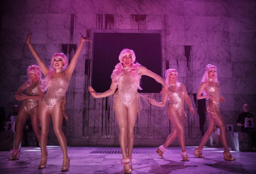 Fem transpersoner i rosa peruker, guldbodys och högklackade skor intar den lilafärgade scenen.