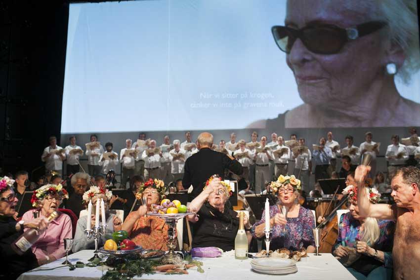 Sju äldre damer med kransar i håret sitter samlade runt ett bord och höjer sina glas. I bakgrunden en stor kör och en skärm föreställandes en närbild på en av damerna i solglasögon.