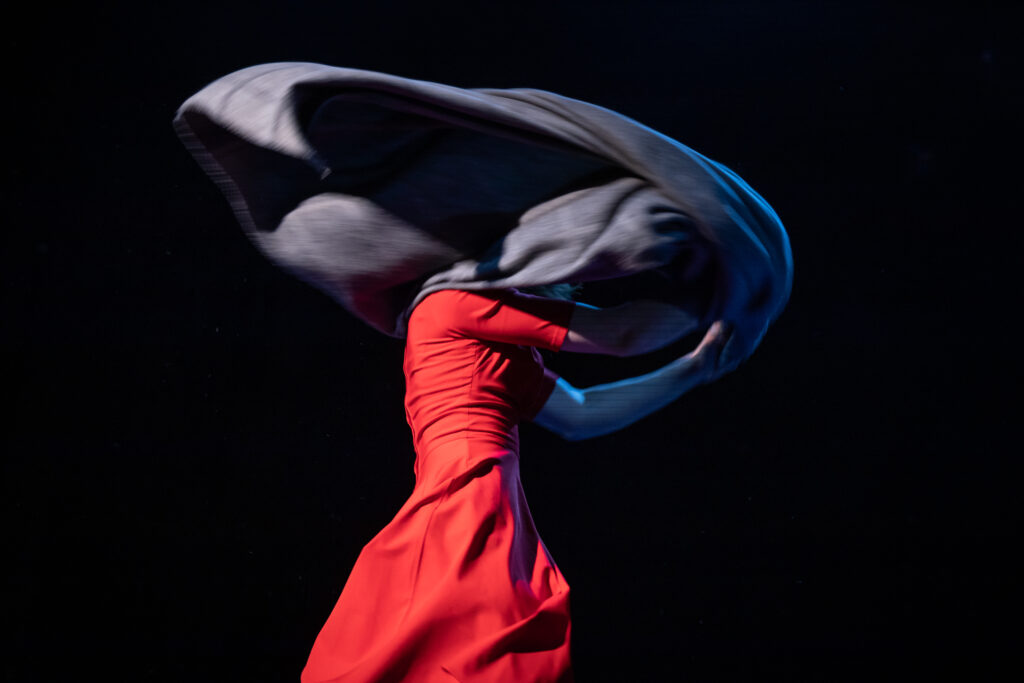 En person i röd klänning snurrar runt. Huvudet skyms av ett fladdrande mörkt tyg.