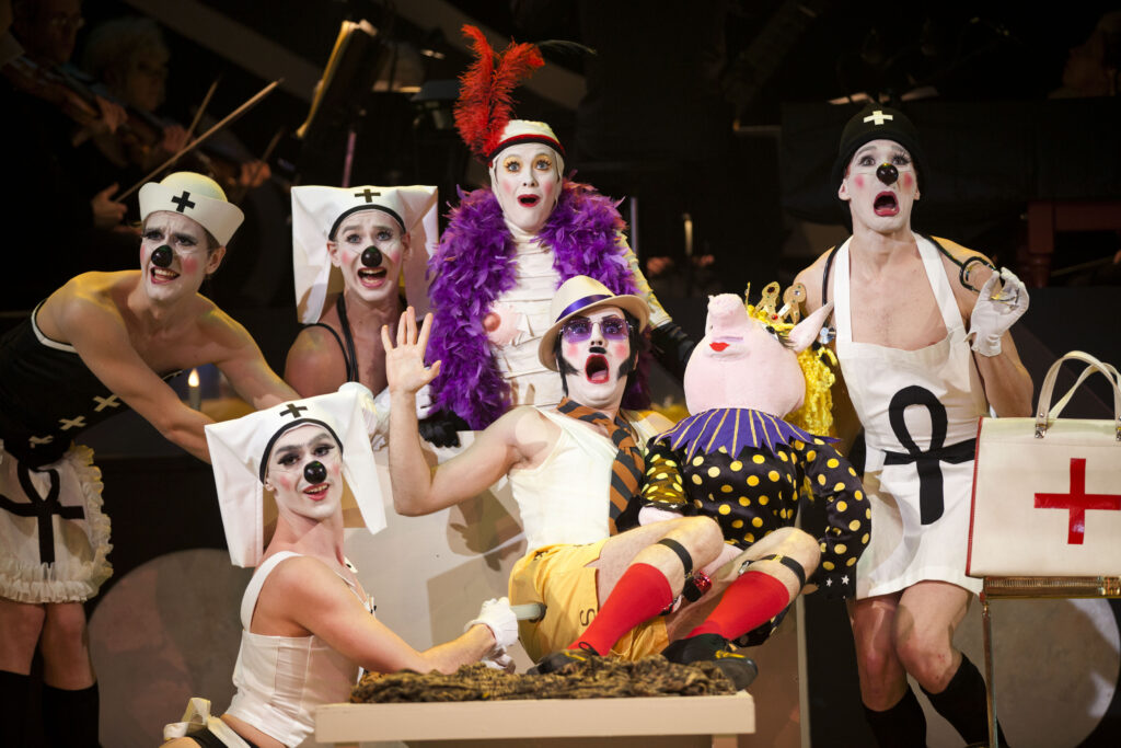 Ett knasigt gäng av fyra sjuksköterskor med svarta clownnäsor. En mumifierad kvinna med lila boa och röd fjäder i håret. Samt en man i hatt med en stor grisdocka i famnen.