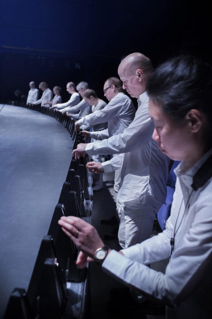 Ett tiotal vitklädda person står på rad vid scenkanten och ställer in en metronom.