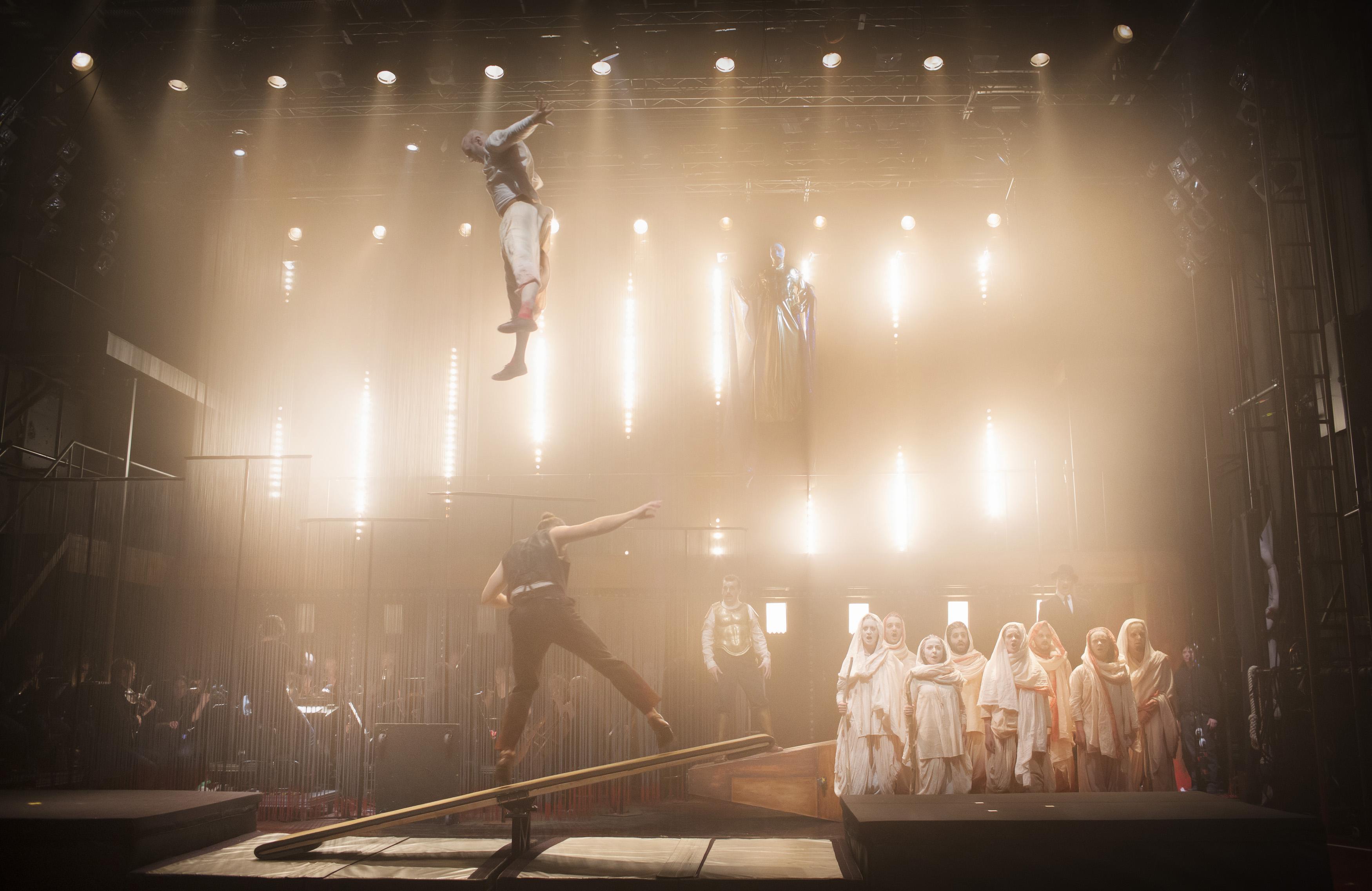 Cirkusartist hoppar upp mot taket på en trampolin. Strålkastarljus i bakgrunden.