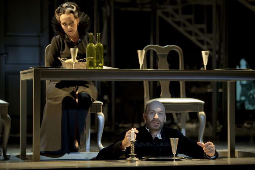 Vid middagsbordet sitter en dam klädd i svart med grå slinga vid tinningen. Under bordet, i ett hål i golvet sitter en man och äter sin middag.