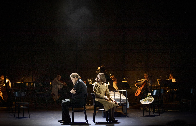 En man och en kvinna sitter i ett dunkelt rum på var sin stol med ryggarna mot varandra. Kvinnan vänder sig om med en besvärad min. Mannen ser nedstämd ut. I bakgrunden en orkester.