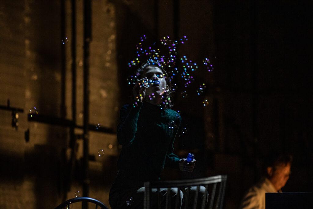 En pojke blåser såpbubblor i ett mörkt rum.