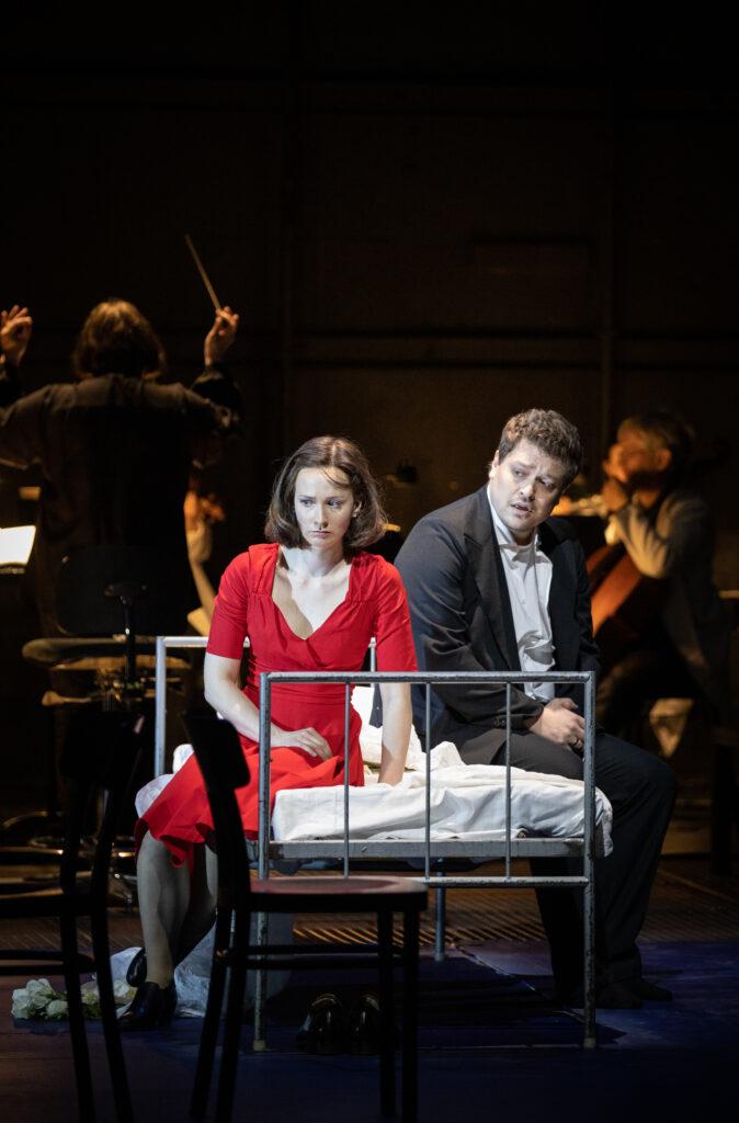 En kvinna i rödklänning och en man i mörk kostym med allvarliga ansiktsuttryck sitter på en sjukhussäng. I bakgrunden en orkester.