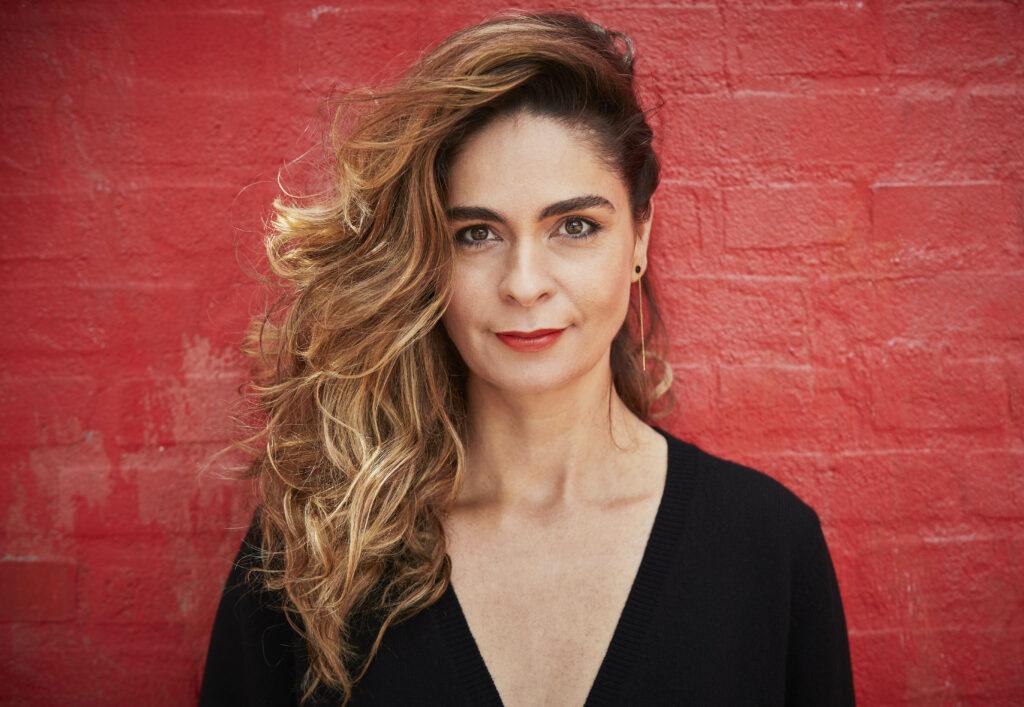 Porträtt av operasångerskan Andrea Pelligrini mot röd tegelvägg.