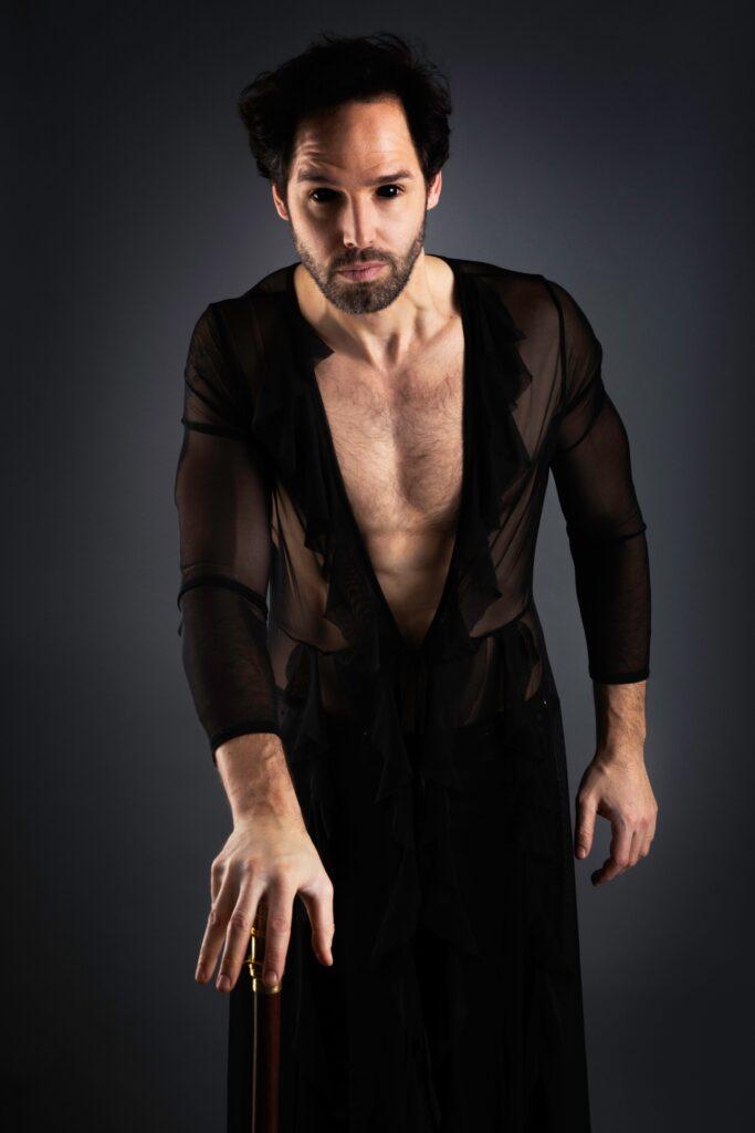 Porträtt av operasångaren Joa Helgesson mot svart bakgrund iklädd svart tunn skjorta med djup urringning och svarta linser.