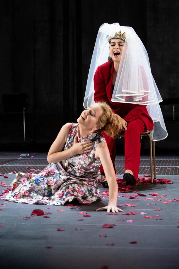 Två välklädda kvinnor roar sig. Den ena i blommig klänning i en teatralisk gest och den andra iklädd röd kostym med brudslöja på huvudet garvar.
