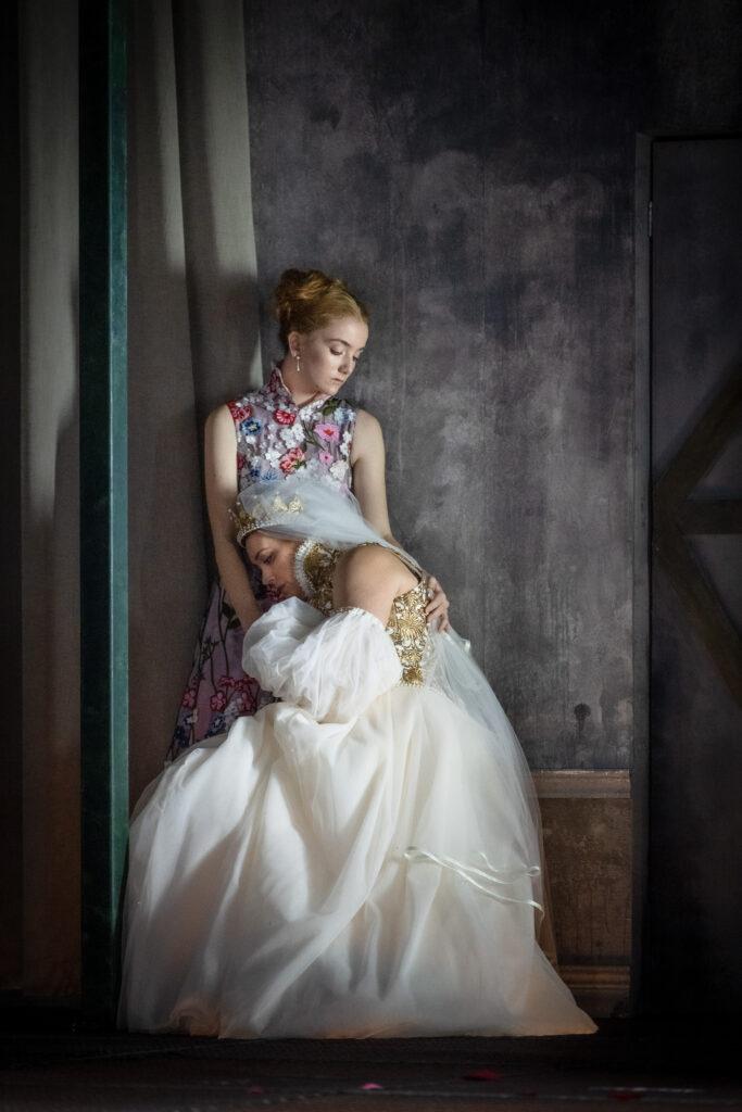 En kvinna i bröllopsklänning vilar olycklig huvudet i knät på en ung finklädd kvinna.
