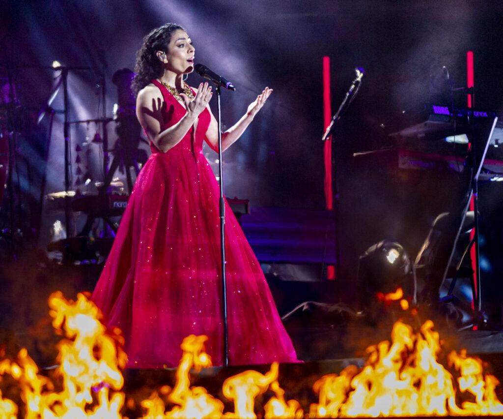 Porträtt av sopranen Negar Zarassi i lång röd klänning  sjungandes på scen.