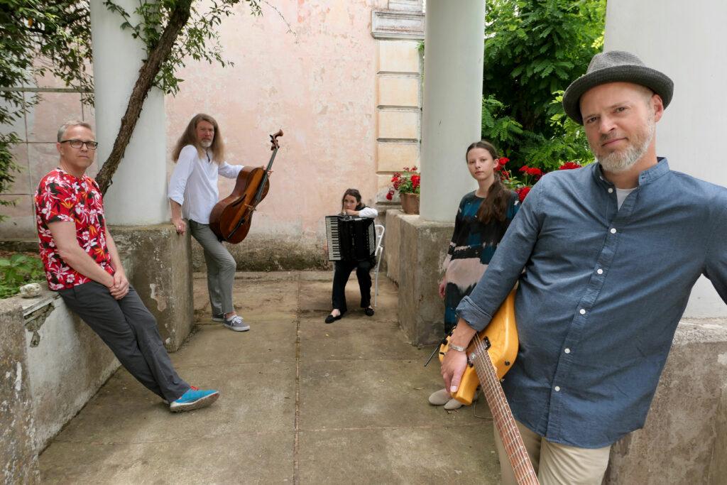 Bandet La Strada står med sina instrument i en trädgård.