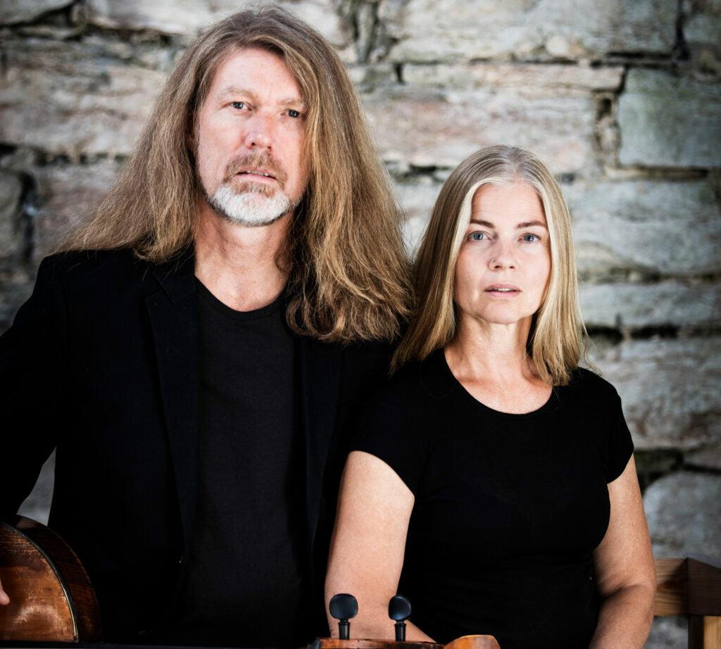 Porträtt av Katarina och Svante Henryson i svarta kläder mot tegelvägg.